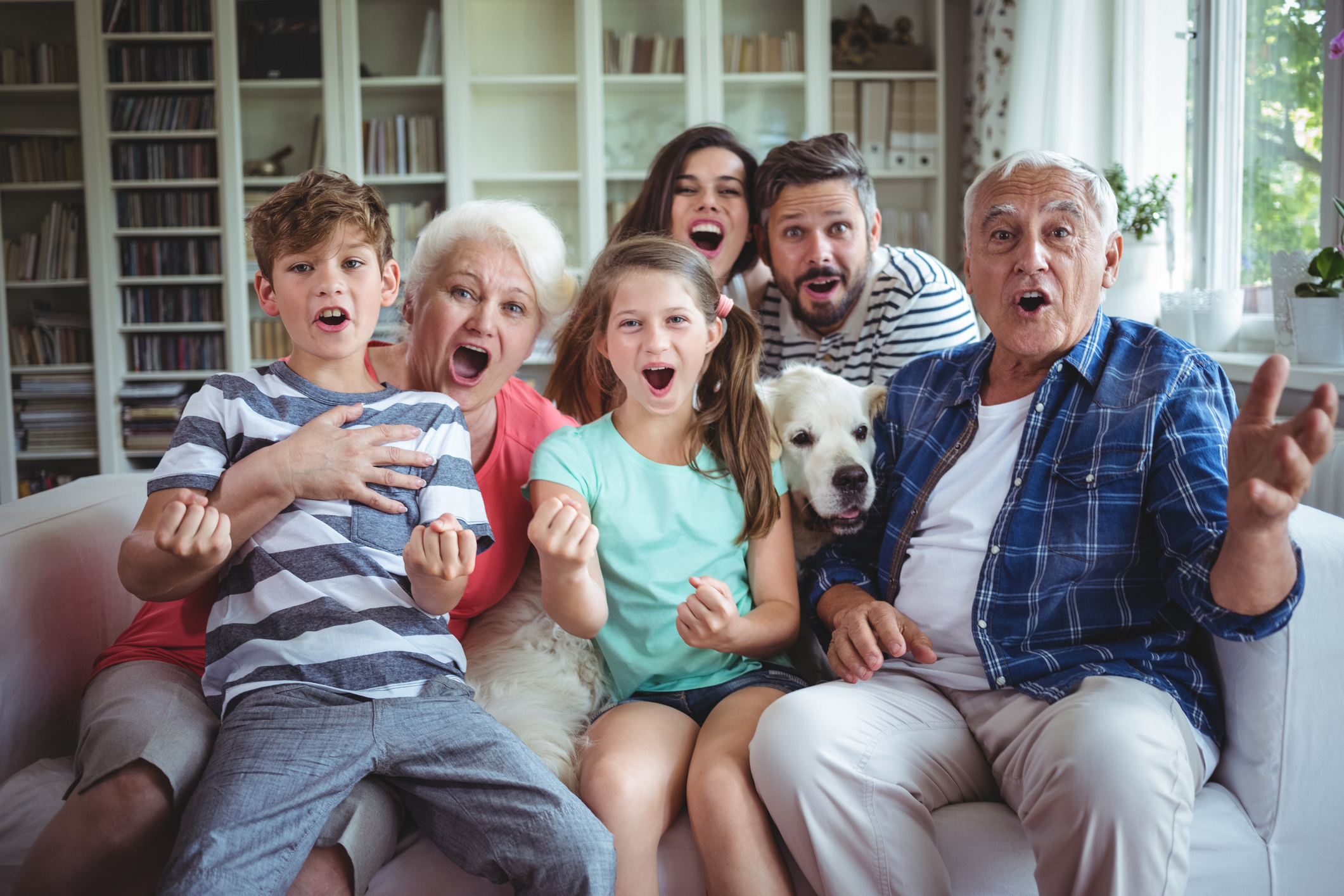 Happy family watching television in living room - PetCareTV